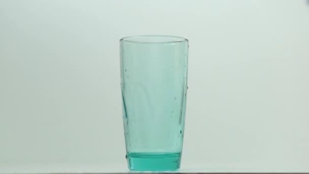 průzračná průsvitná voda proudí shora do skla