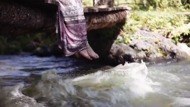 A woman relaxes by the lake, sitting on the edge of a wooden bridge, swinging her feet at the surface of the water. Slow motion. Close-up
