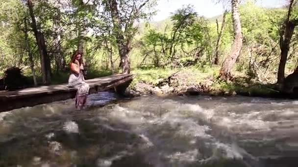 A beautiful girl relaxes by the lake, sitting on the edge of a wooden bridge, swinging her feet at the surface of the water. Slow motion