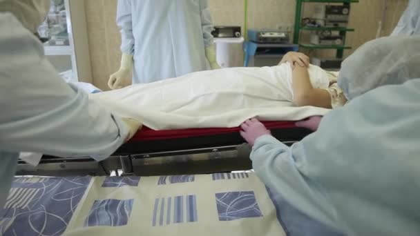 A group of surgeons shift the patient after surgery to a bed for transportation.