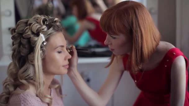 Make-up artist kadeřnice dělá make-up pro módní dívka