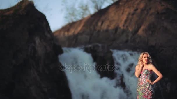 Szép szexi lány ruhában pózol a vízesés nap háttér