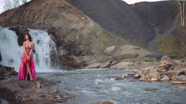 Portrét. Krásná sexy dívka v šatech vystupují proti vodopádu a řeka za slunečného počasí