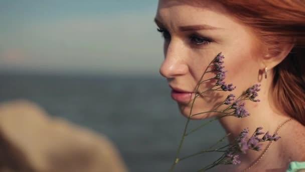 Portré. Szép szexi lány pózol a tenger, a virágok ellen