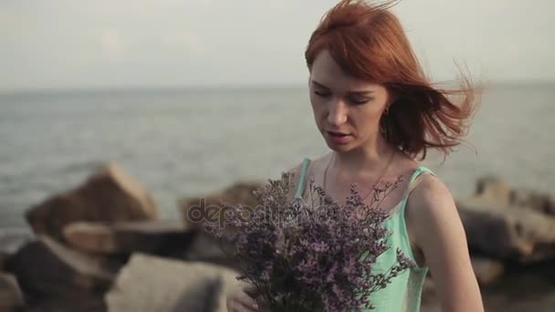 Beautiful sexy girl on the seashore holding flowers