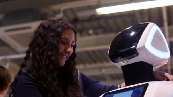 Novosibirsk / Russia - February 17 2018. Corporation of robots.The girl communicates with the robot and smiles. Modern robotic technologies. Artificial intelligence. Cybernetic systems today. HD