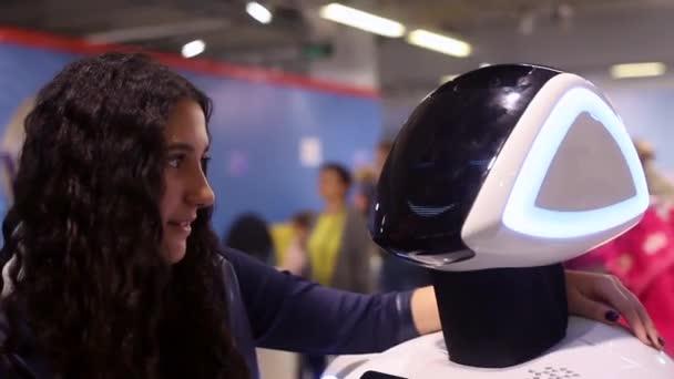Novosibirsk / Oroszország - február 17 2018. Corporation robotok. A lány kommunikál a robot, és mosolyog. Az ember és a robot. Robotika modern technológia. Mesterséges intelligencia. Kibernetikai rendszerek ma. HD