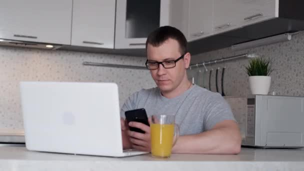 A man during remote work from home writes data from a phone to a laptop while sitting at a table.