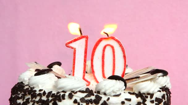 Ünnepi évforduló 10 év torta és gyertyák rózsaszín háttér