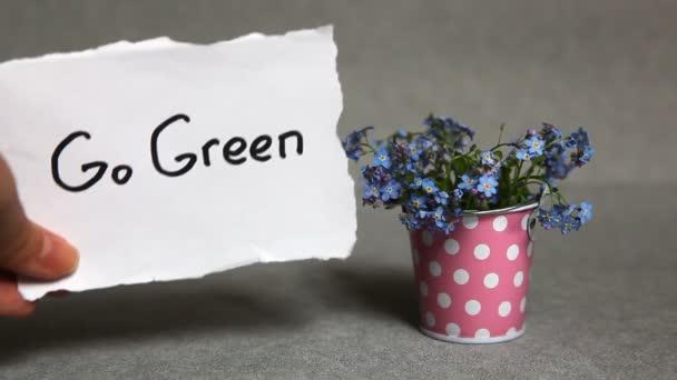 Go green concept, slovo s modrými květy