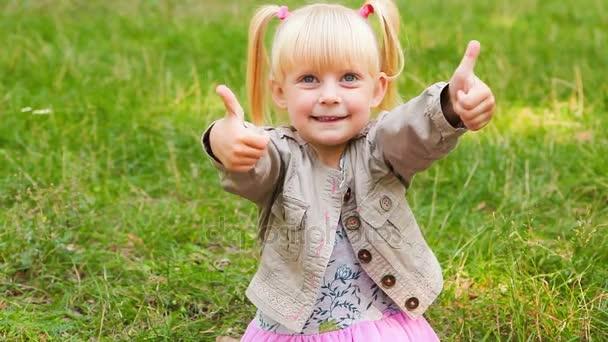 Malá holčička ukazují palce a úsměv