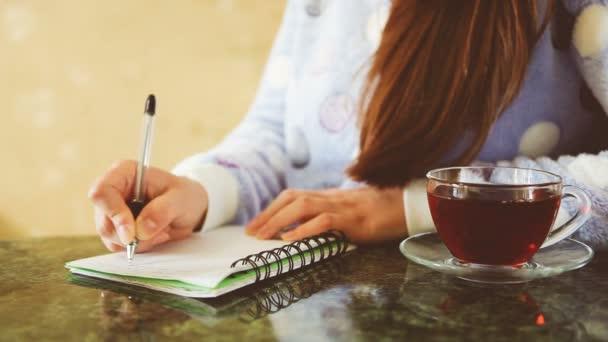 Gyönyörű fiatal nő, napló írás, és ivott tea, diák vagy üzletasszony