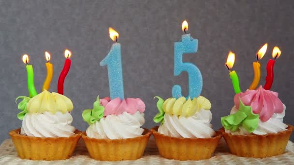 Happy 15 birthday cakes and blue numbers candles on gray background