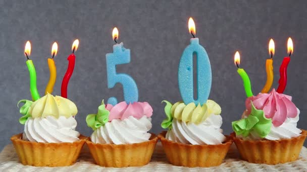 Šťastný, 50 narozeninové dorty a modré číslice svíčky na šedém pozadí