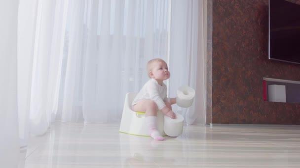 Malé dítě sedí na nočníku a zbavuje sama