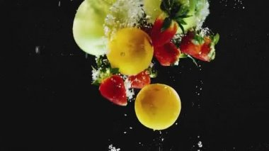 Hodně z pomeranče, jablka, jahody spadající do vody zpomalené