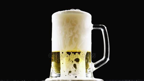 Pivo nalévá do sklenice na černém pozadí. Zpomalený pohyb