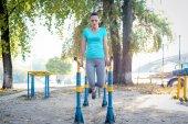 Sportliche Frau turnt am Parallelbarren