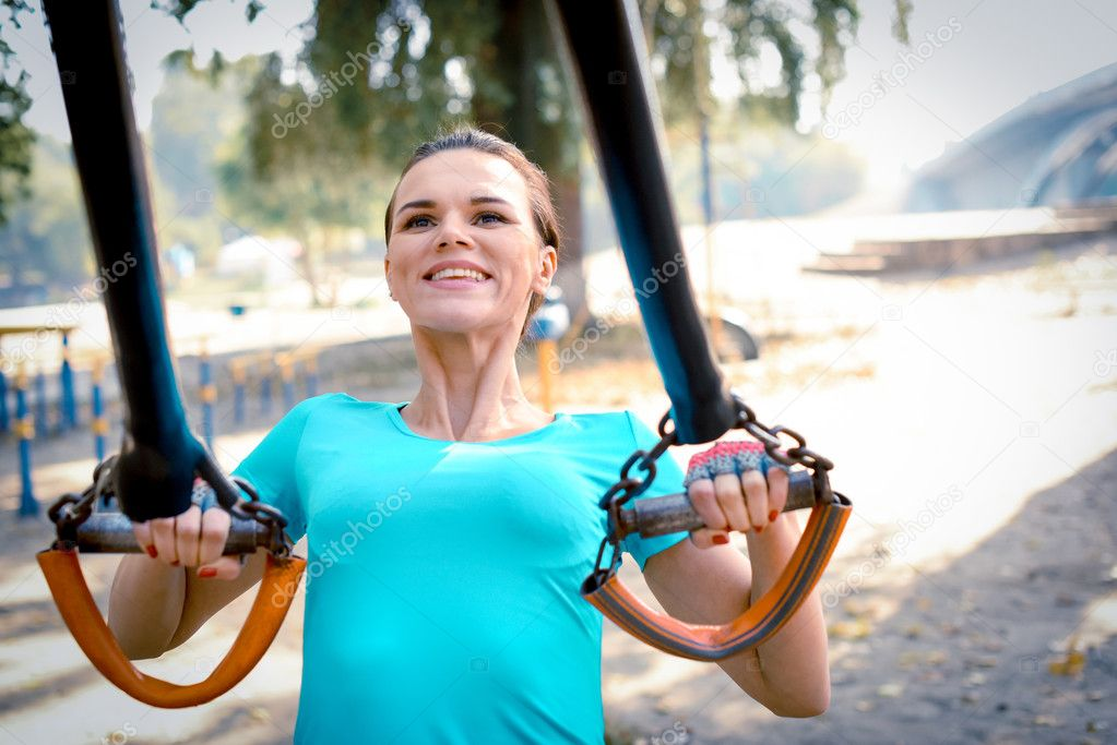 Woman doing exercises in outdoor gym