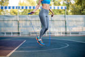 Fotografie Athletic woman exercising with rope jumping