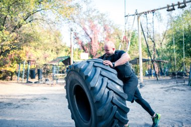 Man with beard lifting tractor tire