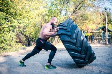 Man lifting a heavy tire