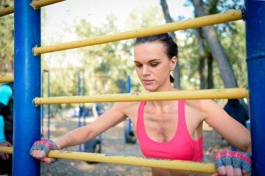 Woman doing exercise at metal bar