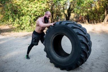 Muscular man working out with heavy tire