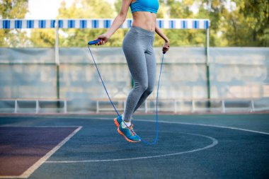 Athletic woman exercising with rope jumping