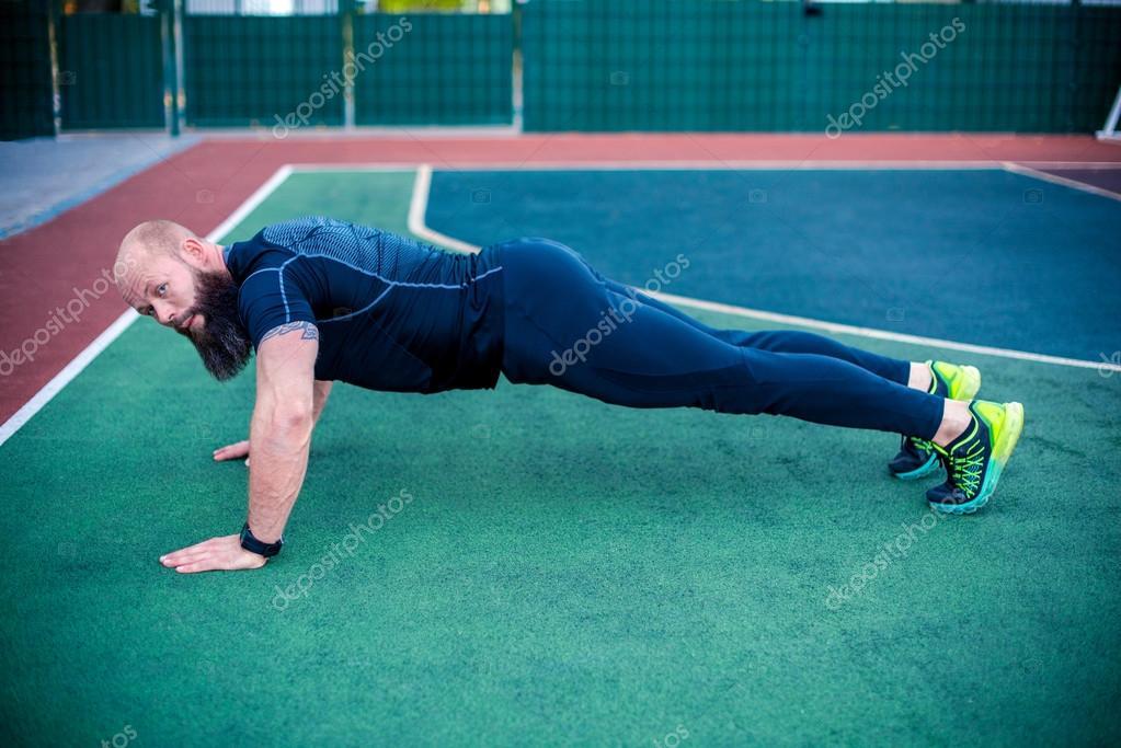 Muscular man doing plank position