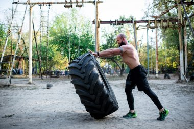 Man lifting large tire