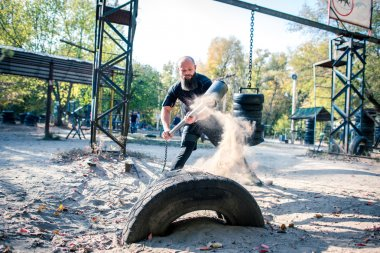 Man hitting a tire with a sledge hammer