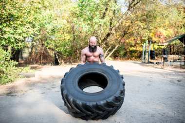 Man lifting a large tractor tire