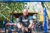 Fényképek Izmos férfi csinál a gyakorlatok a súlyokkal