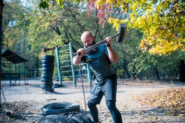 Man hitting tires with sledgehammer