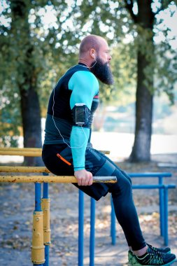 Muscular bearded man on parallel bars