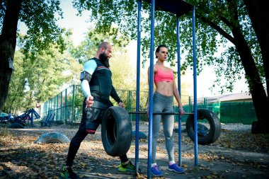 Man encouraging woman in lifting weight