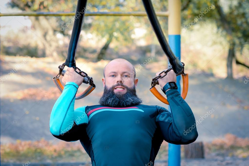Muscular bearded man training with straps