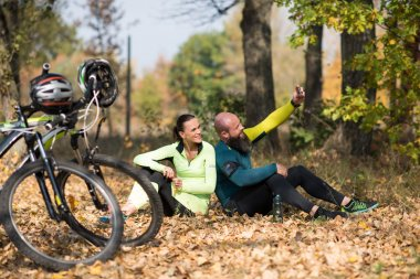 Couple of cyclists taking selfie while sitting and resting in autumn park, bikes on foreground stock vector