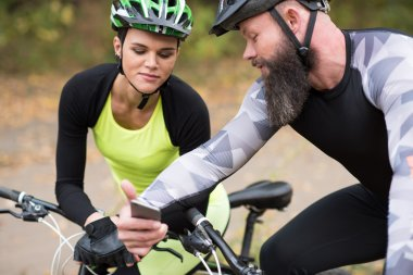 man cyclist showin smartphone to girl