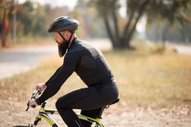 Bearded man cycling in park
