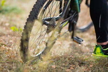 Bicycle with cyclist on dry grass