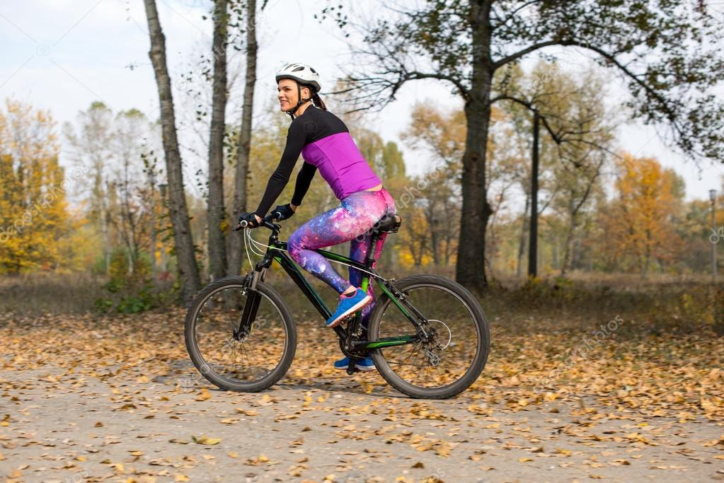 Woman cycling in autumn park