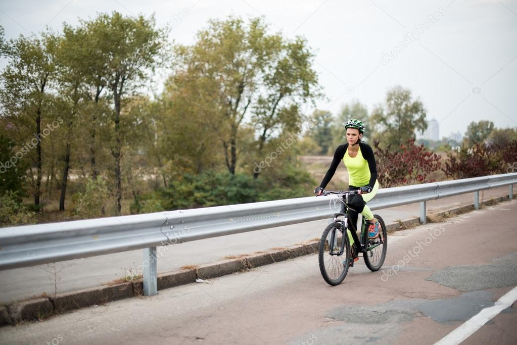 Woman cycling on road