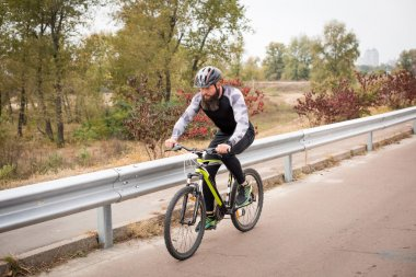 Man cycling in autumn park