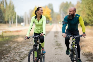 Smiling couple cycling in park