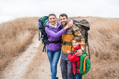 Happy family with backpacks hugging