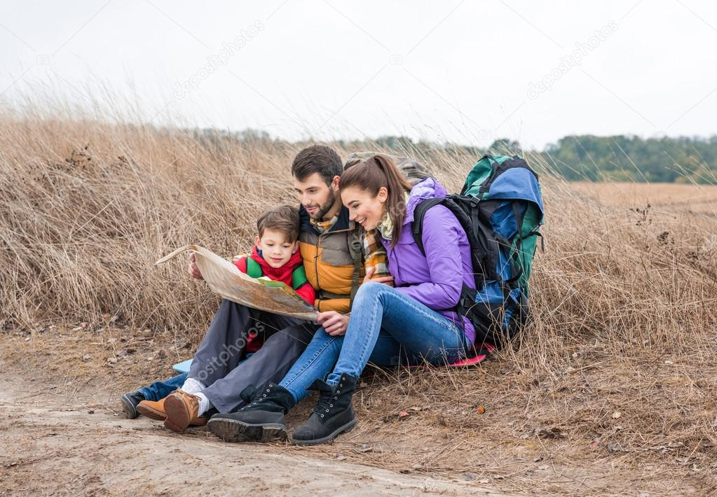 Family with backpacks looking at map