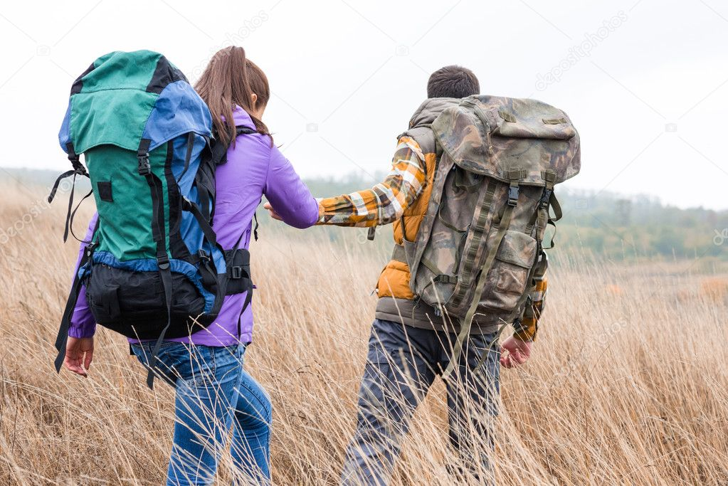 Young couple with backpacks walking in countryside