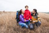 Happy family with backpacks embracing